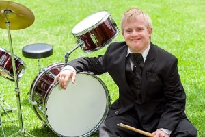 Down syndrome teenager play drum kit